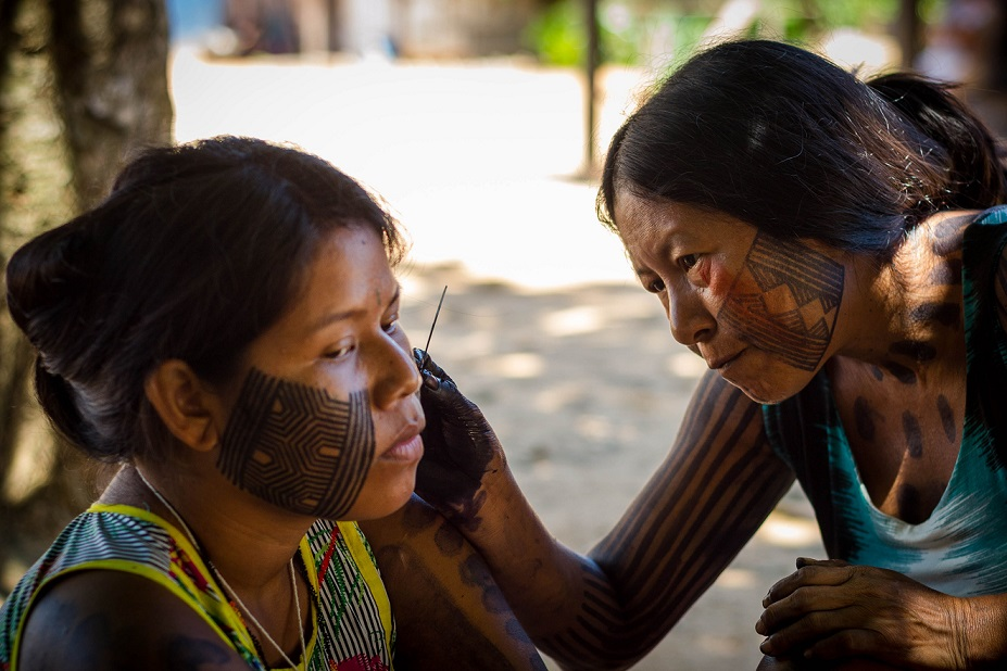 A Mebengokre mother paints the face of her daughter.