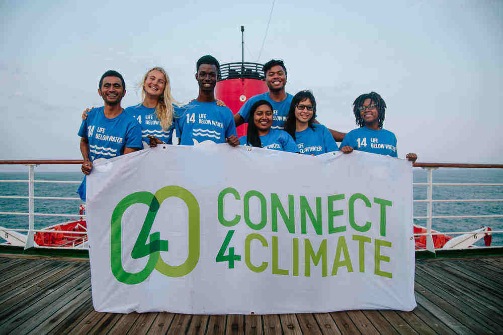 The Ocean and Climate Youth Ambassadors Programme participants took a photo with the Connect4Climate flag while on board the Peace Boat.